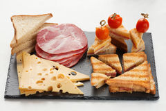 Slices of cheese, ham, bread and hot marinated cherry tomatoes sandwiches. On a slate board Stock Image