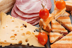 Slices of cheese, ham, bread and marinated cherry tomatoes sandwiches. On a slate board Stock Images