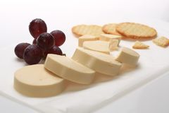 Slices of cheese next to some grapes.  royalty free stock photos
