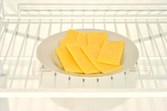 Slices cheese on a plate in a fridge. Some slices cheese on a plate in a fridge Royalty Free Stock Photos