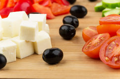 Slices of cheese, tomatoes, peppers, cucumbers and black olives Stock Photos