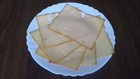 Slices of cheese on white plate stock video