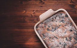 Slices of cherry cake on a cooling hatch with cake in a pan in a background. Cherry cake in a baking pan on a wooden background. Top view Stock Images