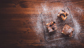 Slices of cherry cake on a cooling hatch with cake in a pan in a background. Slices of cherry cake on a cooling hatch on a wooden background. Top view Stock Photography