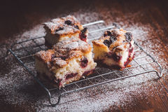 Slices of cherry cake on a cooling hatch. On a wooden background Royalty Free Stock Images