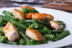 Slices chicken meat with green beans on a white plate Royalty Free Stock Photos
