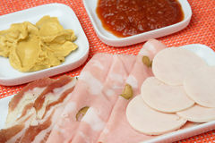 Slices of chicken sausage. Mortadella and bacon on plate Stock Photography