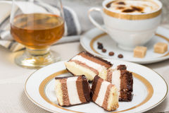 Slices of chocolate cake, brandy and coffee with cream Royalty Free Stock Photos
