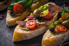 Slices of ciabatta with olives , tomatoes and basil on the black stone table horizontal Royalty Free Stock Images