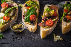 Slices of ciabatta with olives , tomatoes and basil on the black stone table Stock Photography