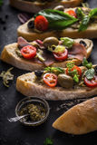 Slices of ciabatta with olives , tomatoes and basil on the black stone table vertical Royalty Free Stock Images