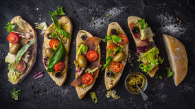 Slices of ciabatta with olives , tomatoes and basil on the black stone table wide screen Stock Photo