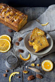 Slices of citrus cake on plate on rustic table with pecan walnuts orange slices Stock Images