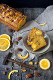 Slices of citrus cake on plate on table with pecan walnuts and orange slices Stock Images