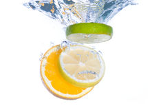 Slices of citrus fruit falling in water Stock Photo
