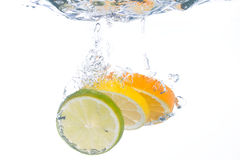 Slices of citrus fruit falling in water stock images