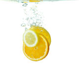Slices of citrus fruit falling in water Royalty Free Stock Photo