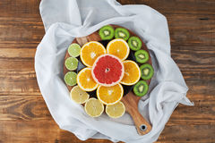 Slices of citrus fruits on chopping board with silk Royalty Free Stock Images