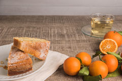 Slices of clementine cake. With powdered sugar topping and cup of chamomile tea. Cake on a plate with fresh clementines on wooden board royalty free stock photos