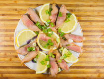 Slices of cold-smoked salmon with lemon and green onion on a pla Stock Images