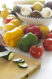 Slices of Courgette. You can see in a white table various vegetables: lemons, tomatoes, onions, garlic, zucchini, peppers, cucumbers, leeks. Some are in a salad Royalty Free Stock Image