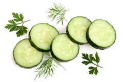 Slices of cucumber with leaf parsley dill on white background.  royalty free stock images
