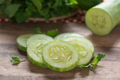 Slices of cucumber on wood cutting board. Royalty Free Stock Image