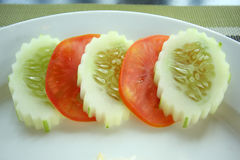 Slices of cucumbers and tomatoes on edge of white plate. Royalty Free Stock Image