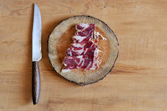Slices of cured jamon on a wooden cutting board Stock Images