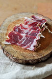 Slices of cured jamon on a wooden cutting board Royalty Free Stock Images