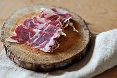 Slices of cured jamon on a wooden cutting board Royalty Free Stock Image