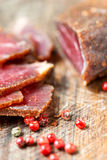 Slices of cured meet and pepper on table Stock Image