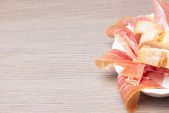 Slices of cured pork ham with bread. Typical spanish tapa: slices of cured pork ham with bread, on a wooden board. Delicious snack Royalty Free Stock Photos