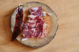 Slices of cured spanish jamon and hot pepper Stock Photos