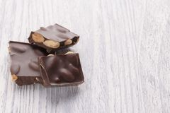 Slices of dark chocolate with nuts on a white wooden table stock images