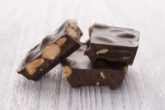Slices of dark chocolate with nuts on a white wooden table royalty free stock photo