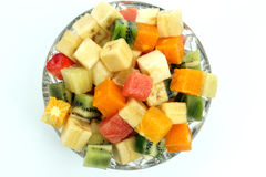 Slices of different fruits in the form of cubes in a plate on wh Royalty Free Stock Photo