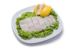 Slices of dory fish with salad and lemon on white plate. Deliciously Royalty Free Stock Photography