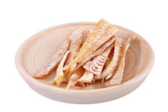 Slices of dried fish on wooden plate isolated over white. Stock Photography