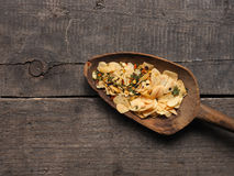 Slices of dried garlic with spicy herbs , view from above. Slices of dried garlic with spicy herbs on an old used wooden spoon, Italian cooking ingredients royalty free stock photography