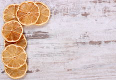 Slices of dried lemon on old wooden background, copy space for text Stock Photo