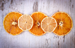 Slices of dried lemon and orange on old wooden background Royalty Free Stock Images