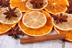 Slices of dried lemon, orange and spices on old wooden background Stock Photo