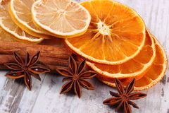Slices of dried lemon, orange and spices on old wooden background Stock Images