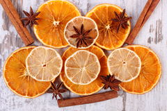 Slices of dried lemon, orange and spices on old wooden background Stock Photography