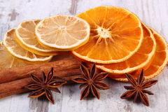 Slices of dried lemon, orange and spices on old wooden background Stock Image