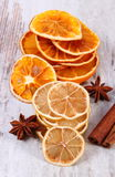 Slices of dried lemon, orange and spices on old wooden background Royalty Free Stock Image