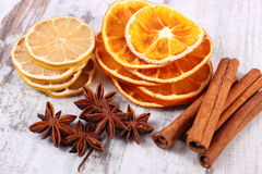 Slices of dried lemon, orange and spices on old wooden background Stock Photos