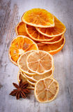 Slices of dried lemon, orange and star anise on old wooden background Royalty Free Stock Images