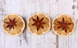Slices of dried lemon and star anise on old wooden background Royalty Free Stock Images